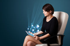 Woman looking at modern tablet with social icons Royalty Free Stock Image