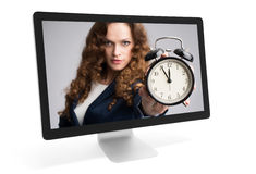 Woman looking through monitor and showing alarm clock Stock Photography
