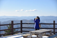 Woman looking at the mountain at winter from pier. Royalty Free Stock Photography