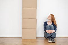 Woman Looking at Moving Boxes. A young woman looking at a tall stack of moving carton boxes while sitting on the floor of an empty room Royalty Free Stock Photo