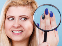 Woman looking at nails through magnifying glass Royalty Free Stock Image