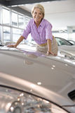 Woman looking at new cars in showroom royalty free stock image