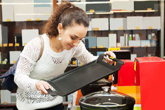 Woman looking for new pan and pot. Happy woman looking for new pan and pot in supermarket royalty free stock photo