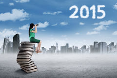 Woman looking at numbers 2015 with binoculars Royalty Free Stock Photo
