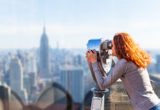 Woman looking in observation binoculars. Red-haired young woman looking at the panorama of the city in an observation coin operated binoculars stock photo