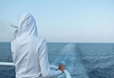 Woman looking at the ocean. Young woman looking at the ocean from a fast going liner Royalty Free Stock Photos