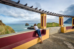 Woman looking at the ocean from special viewpoint spot in Porto da Cruz, Madeira. royalty free stock images