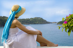 Woman looking at an ocean view. Woman with a sun hat looking at a breathtaking ocean view Stock Image