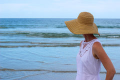 Woman Looking At Ocean. Woman in white dress at beach looking out at the ocean Royalty Free Stock Photography