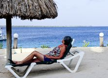 Woman looking at the Ocean. Woman in a beach chair looking at the Ocean royalty free stock images