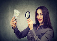 Woman looking at one hundred dollar bills through magnifying glass stock photography