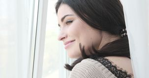 Woman looking out through apartment window. Beautiful young woman looking out through apartment window stock video
