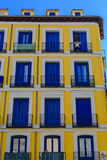 A woman looking out of the balcony of a block of appartments Stock Photo