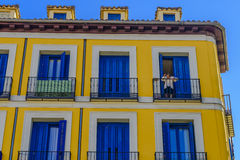 A woman looking out of the balcony of a block of appartments Stock Image