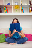 Woman looking out from behind of the book Royalty Free Stock Photos