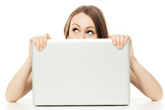 Woman looking out from behind a laptop Stock Photos