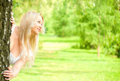 Woman looking out from behind the tree Stock Photography