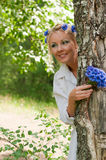 Woman looking out from behind a tree Royalty Free Stock Image