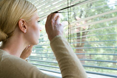 Woman looking out of blinds Royalty Free Stock Images