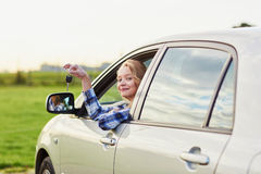 Woman looking out of the car window and holding a key Stock Photo