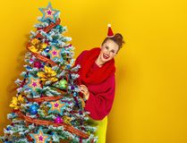 Woman looking out from Christmas tree on yellow background Royalty Free Stock Image