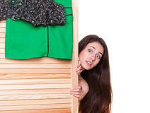 Woman looking out of clothes screen. Amazed young woman looking out of clothes screen Stock Image