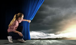Woman looking out from curtain stock photo