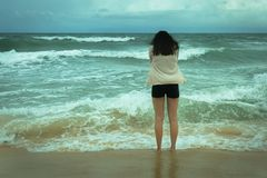 Sad depressed lonely woman standing on ocean shore crying, ready to give up. Woman looking out in despair at a gloomy ocean shoreline with faded colors stock photo