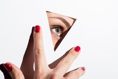 Woman looking out of hole in paper. Close-up shot of woman looking out of hole in white paper and touching it with hand Royalty Free Stock Images