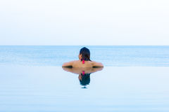 Woman looking out from infinity swimming pool Stock Images