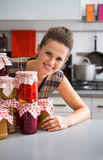 Woman looking out from jars  in kitchen Stock Images