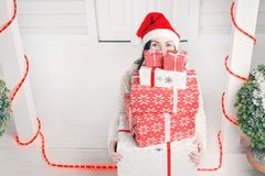 Woman looking out from pile of Christmas gift boxes Royalty Free Stock Photo