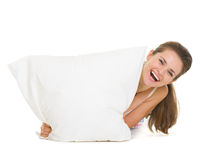 Woman looking out from pillow isolated on white Stock Image