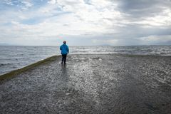 Woman standing at end of boat ramp stock images