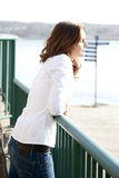 Woman looking out to sea. Side view of young woman with dreamy expression looking out to sea Stock Photography