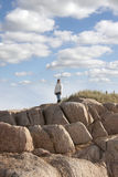 Woman looking out to sea a top of old rock formation Royalty Free Stock Images