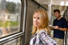 Woman looking out the train window smiling Stock Photos