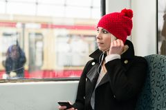 Woman looking out of train window using phone Royalty Free Stock Image