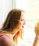 Woman looking out through venison blinds Stock Photos