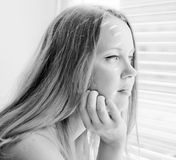 Woman looking out through venison blinds Royalty Free Stock Image