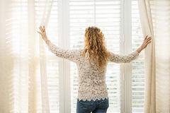 Woman looking out window. Woman looking out big bright window with curtains and blinds royalty free stock photo