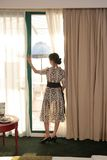 Woman looking out of window. In hotel room Stock Photos