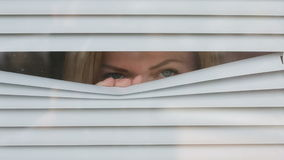 Woman looking out the window through the blinds to the street, spying. suspected