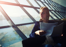 Woman looking out the window and holding a report. Portrait of young elegant woman sitting in modern office interior holding papers and pensively gazing out of royalty free stock images