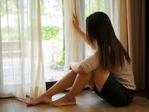 Woman looking out a window, indoors. Rear view of a young woman holding the curtains open to look out of a large light window at home, interior. Positive and Stock Photography