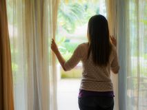 Woman looking out a window, indoors. Rear view of a young woman holding the curtains open to look out of a large light window at home, interior. Positive and Royalty Free Stock Image