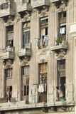 Woman looking out window at laundry of dilapidated balcony in Havana, Cuba Royalty Free Stock Photography