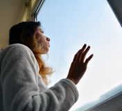 Woman looking out the window. Sad woman looking out the window at the snowy weather outside royalty free stock photos