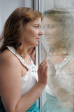 Woman looking out of window Royalty Free Stock Photography