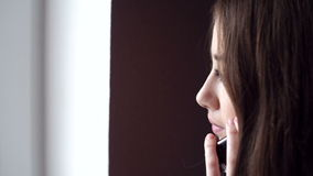 Woman looking out the window and talking on the phone stock footage